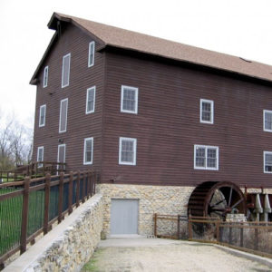 brown mill with stone foundattion and water wheel